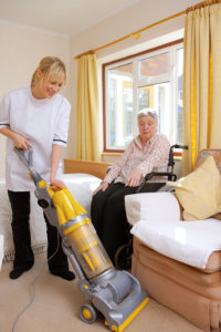 Woman vacuuming while senior woman on a wheelchair watch