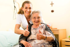 caregiver and sonior woman giving thumbs up